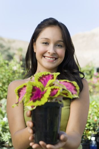 Portrait of a happy young woman holding potted plant at botanical garden