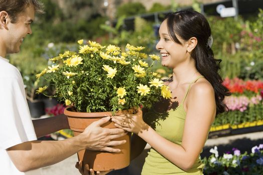 Young woman buying potted plant from gardener at botanical garden
