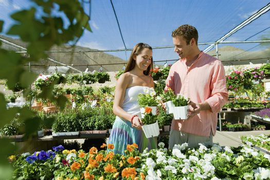 Happy couple selecting potted flower plants at botanical garden