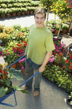 Full length portrait of a handsome man with wheelbarrow at botanical garden