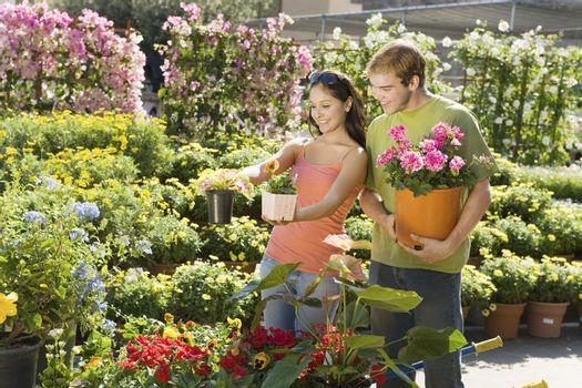 Young couple selecting potted plants at botanical garden