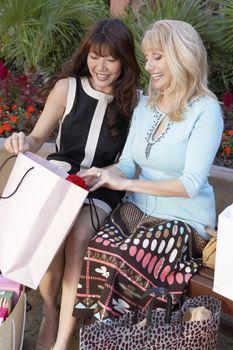 Happy shopaholic women checking bags