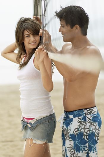 Multiethnic couple looking at each other while standing by the net