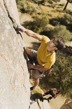 Full length of determined man climbing rock