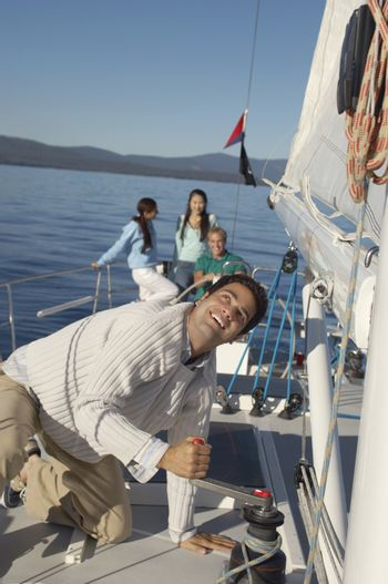 Man turning the winch of a sailboat with friends in the background