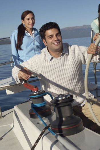 Man holding the steering of sailboat with friend in the background