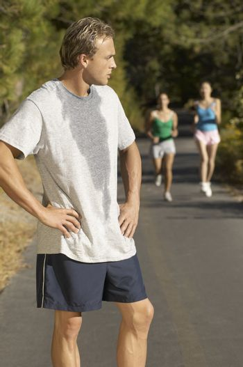 Male jogger pausing for breath on path with female friends in background