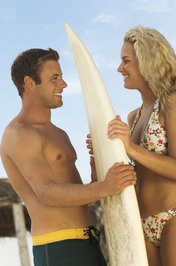 Happy couple looking at each other as they hold a surfboard