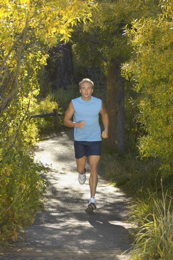 Full length of a middle aged man jogging on a forest pathway