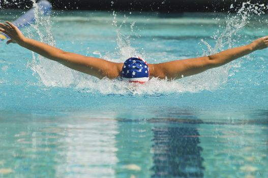 Female athlete performs a butterfly stroke during a swimming race