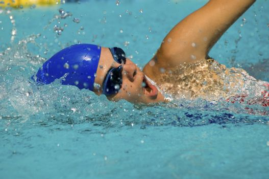 Competitive swimmer doing a freestyle stroke in a swimming pool