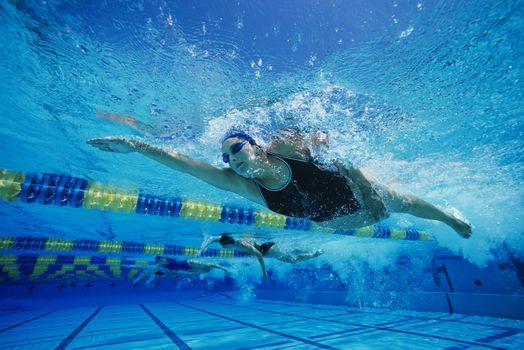 Female swimmers racing underwater in pool