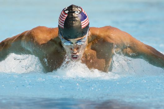 Closeup of a young man swimming butterfly stroke