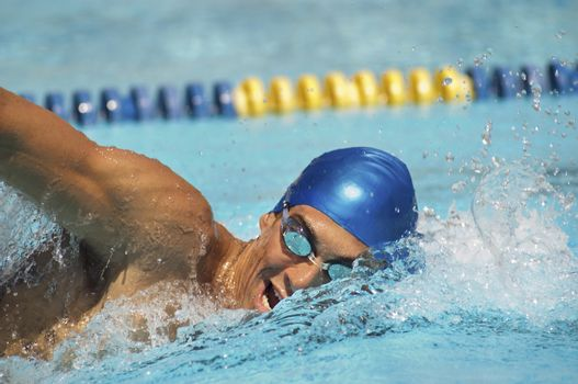 Male participant swimming in a freestyle during swimming race