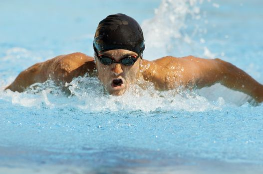Competitive male swimmer in motion during swimming race
