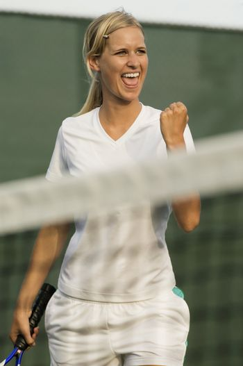 Female tennis player cheering with clenched fist for scoring points