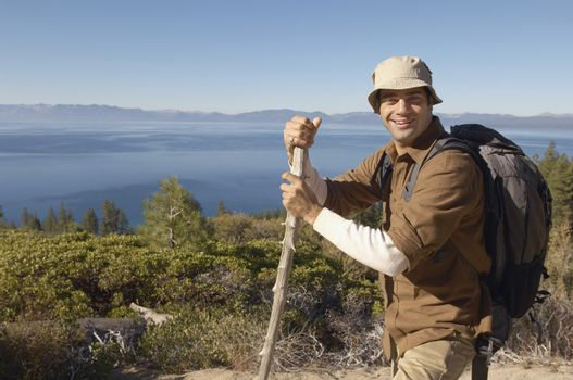 Portrait of smiling young man with hiking pole on coastal track