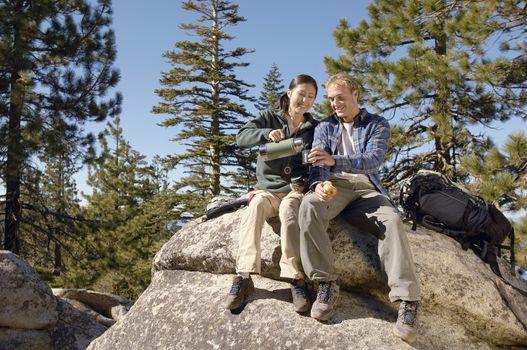 Full length of couple sitting on rock