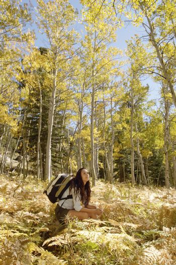 Young woman with backpack resting in forest