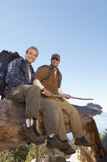 Full length portrait of two male hikers sitting on log