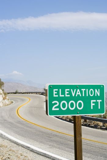 Elevation road sign with road in the background