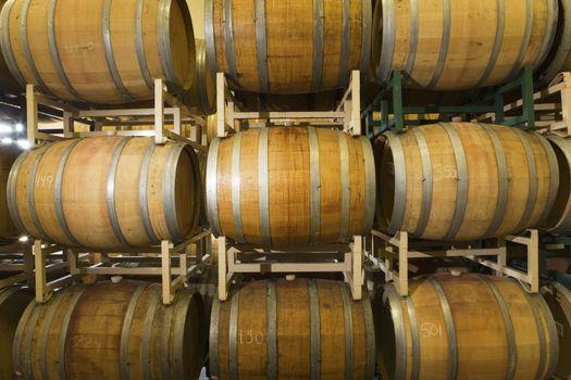 Rows of wooden wine barrels in winery cellar