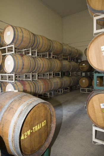 Stack of wine barrels on a stand stored in an old cellar of the winery
