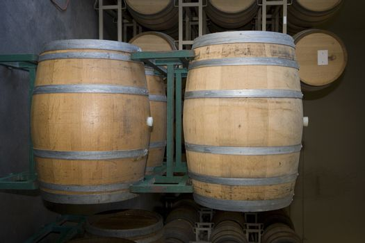 Wooden wine barrels stored in an old cellar of the winery