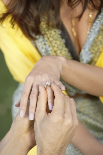 Close up of a man placing a diamond engagement ring to a women's finger