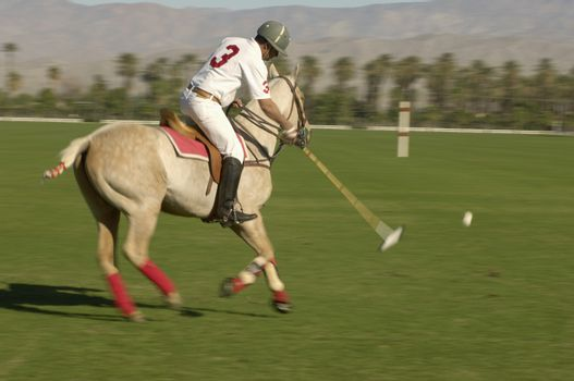 Blurred motion of polo player swinging at ball