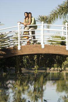 Full length of loving couple on bridge