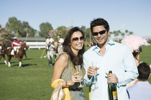 Couple toasting on polo field portrait