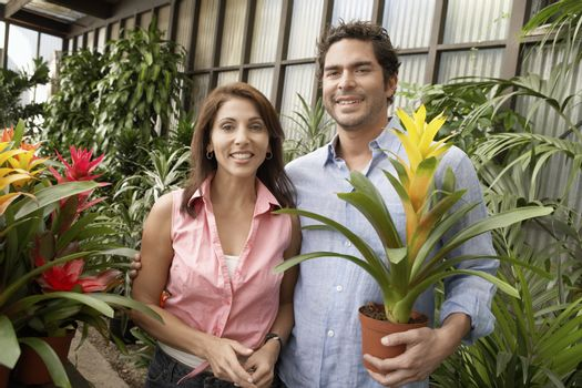 Portrait of happy mature couple holding potted plant at botanical garden