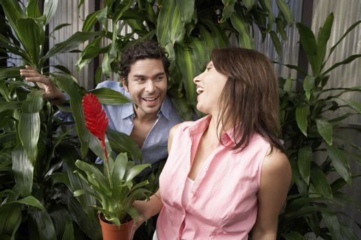 Cheerful mature couple with potted plant at botanical garden