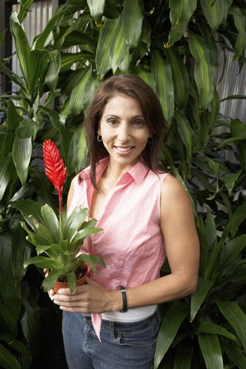 Portrait of happy mature woman holding potted plant at botanical garden