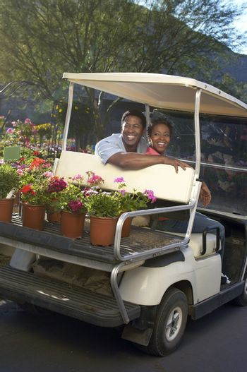Happy African American couple in golf cart at botanical garden
