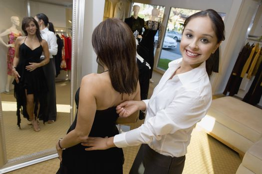 Mature woman trying on dress with helpful assistant in clothes store