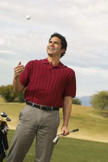 Happy mature man holding golf club while tossing ball