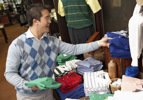 Happy Chinese man buying shirts in clothing store