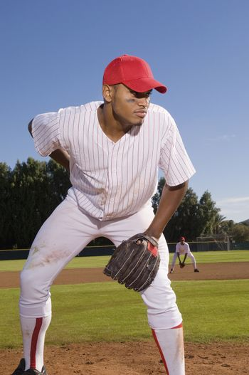 Young baseball pitcher playing on field with team mate in the background