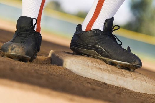 Low section of a baseball player standing base