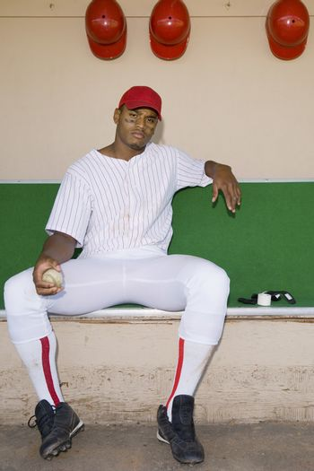 Portrait of a confident African American baseball pitcher sitting in the dugout