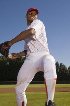 Young baseball pitcher winding up to throw the baseball