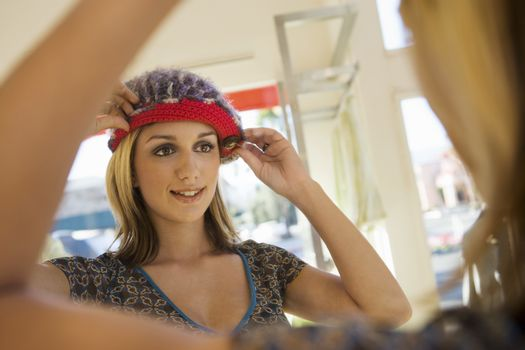 Happy young woman adjusting knit cap in front of mirror at store