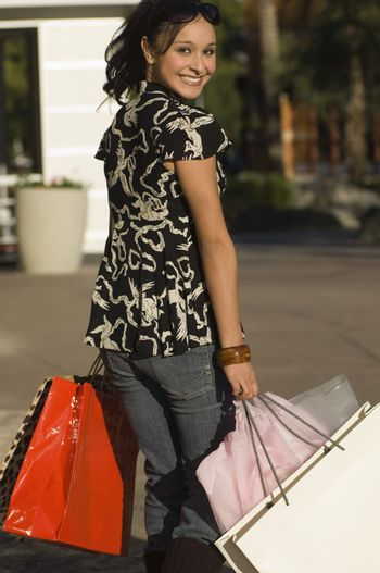 Portrait of a shopaholic young woman with bags looking over shoulder