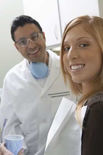 Portrait of a woman holding disposable cup with dentist in the background