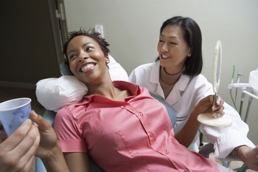 Happy female patient holding disposable cup while dentist looking at her