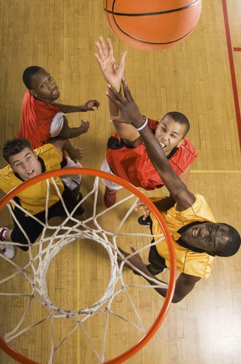 High angle view of basketball player attempting to slam dunk ball