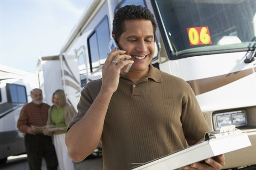Mature tourist guide talking on phone while holding a book with passengers in background