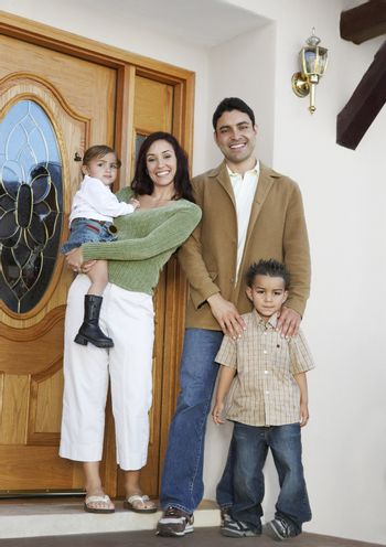 Full length portrait of a happy family at the entrance of new house